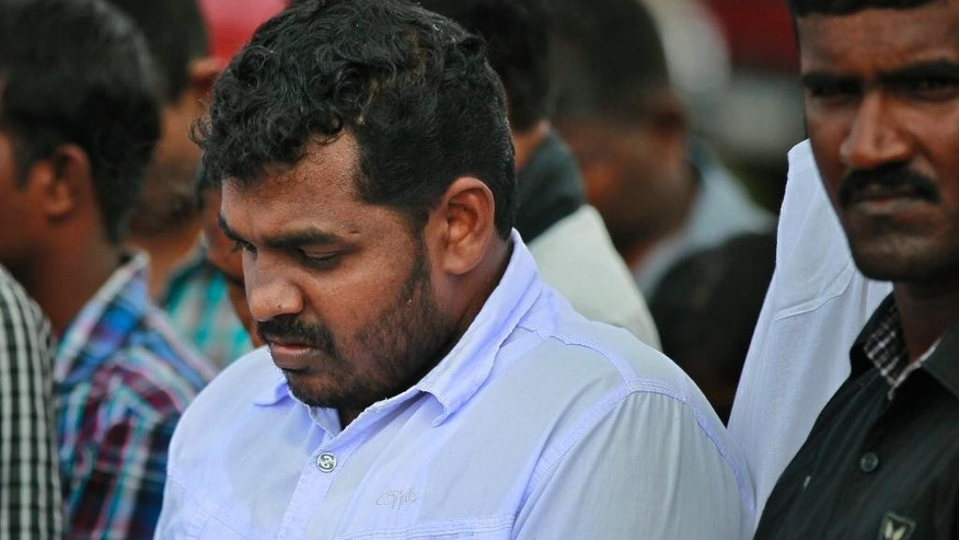 A Sri Lanka's ethnic Tamil political activist observes silence near a makeshift monument, where thousands of people were killed in fierce fighting between the army and Tamil Tiger rebels, in Mullivaikkal, about 335 kilometers (208 miles) northeast of Sri Lanka, Monday, May 18, 2015. Sri Lanka's ethnic Tamil politicians and a few civilians have gathered under heavy surveillance at a ceremony to pay homage to thousands of people killed in the final days of a decades-long civil war that ended in 2009. (AP Photo/Eranga Jayawardena)