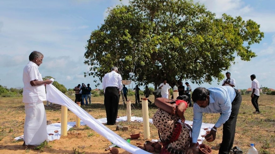 Sri Lanka's ethnic Tamil political activists prepare a makeshift monument, where thousands of people were killed in fierce fighting between the army and Tamil Tiger rebels, in Mullivaikkal, about 335 kilometers (208 miles) northeast of Sri Lanka, Monday, May 18, 2015. Sri Lanka's ethnic Tamil politicians and a few civilians have gathered under heavy surveillance at a ceremony to pay homage to thousands of people killed in the final days of a decades-long civil war that ended in 2009. (AP Photo/Eranga Jayawardena)