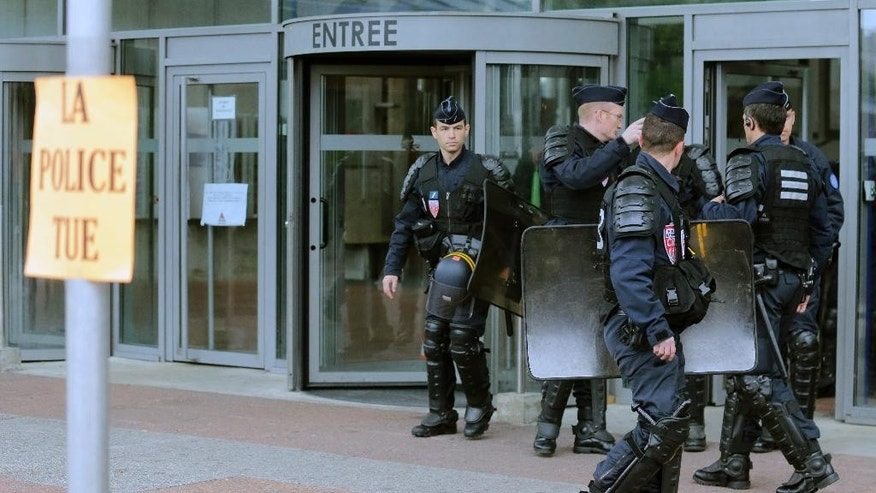 "Police stand guard outside the courthouse in Bobigny, suburban Paris, France, Monday May 18, 2015. A French court on Monday acquitted two police officers accused of contributing to the deaths of two minority teenagers in a blighted Paris suburb a decade ago — a long-awaited verdict that crushed the boys' families and raised fears of possible violence like that seen recently in the U.S. The deaths of 15-year-old Bouna Traore and 17-year-old Zyed Benna prompted weeks of riots across France in 2005, exposing anger and resentment in neglected, crime-ridden suburban housing projects. Placard reads: "" Police kills'. (AP Photo/Jacques Brinon)"