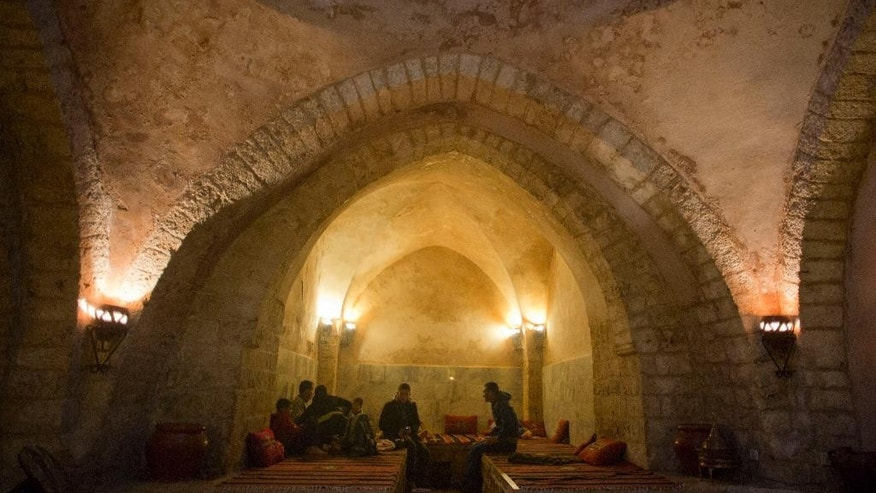 In this Saturday, May 2, 2015, photo, Palestinians rest at the reception of Hamam al-Sumara a historic bathhouse in Gaza City. After dawn prayers in Gaza, a few dozen men descend a metal staircase to gather in the steamy confines of Hamam al-Sumara, a centuries-old bathhouse where residents of the isolated territory find respite and relief.  (AP Photo/Khalil Hamra)