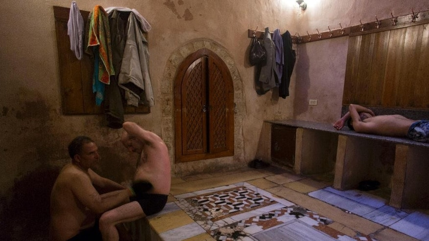 In this Saturday, May 2, 2015, photo, Palestinians rest outside the steam room in Hamam al-Sumara bathhouse in Gaza City. Historic bathhouses like this one can be found across the Middle East, where they preserve a tradition of public bathing that goes back to ancient times. Hamam al-Sumara, Arabic for the Samaritans' Bath, dates back 1,000 years but has been renovated, most recently in the 1990s by the Palestinian Authority.  (AP Photo/Khalil Hamra)