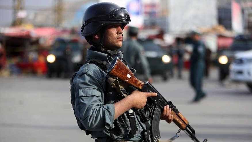 A member of the Afghan security forces stands guard at the site of a suicide car bombing attack in Kabul, Afghanistan, Tuesday, May 19, 2015. A large suicide car bombing struck downtown Kabul on Tuesday afternoon, apparently targeting justice ministry employees and killing several people, an Afghan official said. The attack happened in the car park of the Justice Ministry when a car packed with explosives was detonated, said Interior Ministry spokesman Sediq Sediqqi. (AP Photo/Rahmat Gul)