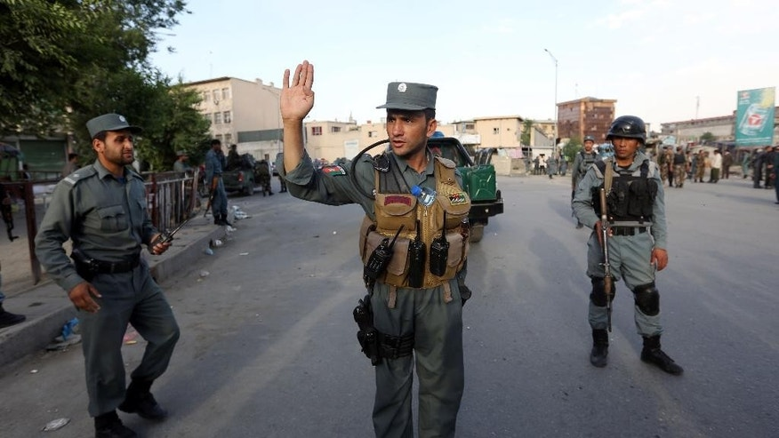 Afghan security forces stand guard at the site of a suicide car bombing attack in Kabul, Afghanistan, Tuesday, May 19, 2015. A large suicide car bombing struck downtown Kabul on Tuesday afternoon, apparently targeting justice ministry employees and killing several people, an Afghan official said. The attack happened in the car park of the Justice Ministry when a car packed with explosives was detonated, said Interior Ministry spokesman Sediq Sediqqi. (AP Photo/Rahmat Gul)