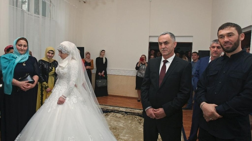 FILE In this Saturday, May 16, 2015 file photo a bride, Chechen Kheda Goilabiyeva, and fiancé, Chechen police officer Nazhud Guchigov, second right, stand in a wedding registry office in Chechnya's provincial capital Grozny, Russia, Saturday, May 16, 2015. A 46-year-old Chechen police officer taking a 17-year-old as his second wife in flagrant violation of Russian laws has caused a storm in the Russian media and put the region's ruler on the defensive. At right is head of the Chechen leader's administration Magomed Daudov. (AP Photo, FILE)