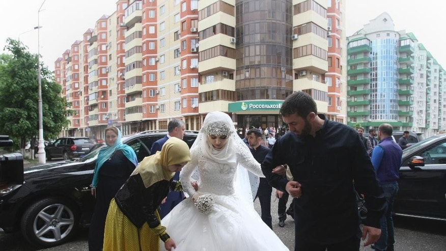 FILE In this Saturday, May 16, 2015 file photo a bride, Chechen Kheda Goilabiyeva, is taken by head of the Chechen leader's administration Magomed Daudov to a wedding registry office for her wedding with Chechen police officer Nazhud Guchigov, in Chechnya's provincial capital Grozny, Russia. A 46-year-old Chechen police officer taking a 17-year-old as his second wife in flagrant violation of Russian laws has caused a storm in the Russian media and put the region's ruler on the defensive. (AP Photo, FILE)