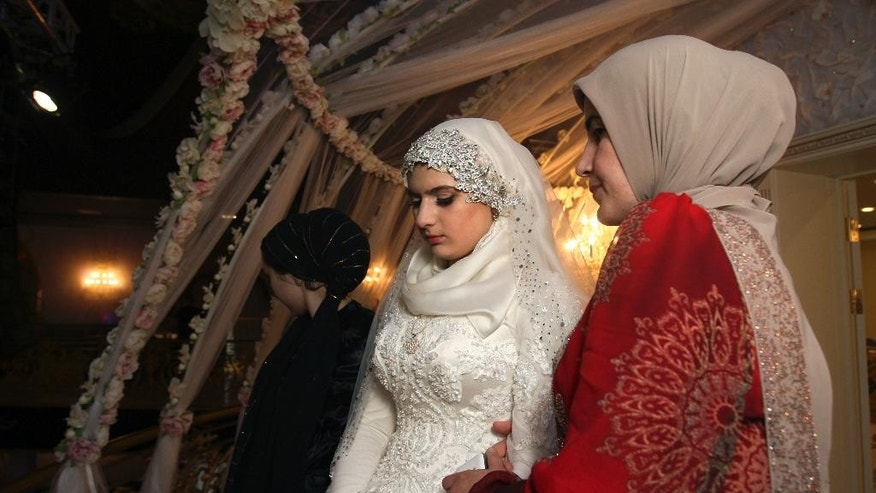 FILE- Saturday, May 16, 2015 file photo Chechen Kheda Goilabiyeva, second right, stands after her wedding with  Chechen police officer Nazhud Guchigov, in Chechnya's provincial capital Grozny, Russia, Saturday, May 16, 2015. A 46-year-old Chechen police officer taking a 17-year-old as his second wife in flagrant violation of Russian laws has caused a storm in the Russian media and put the region's ruler on the defensive. (AP Photo, File)