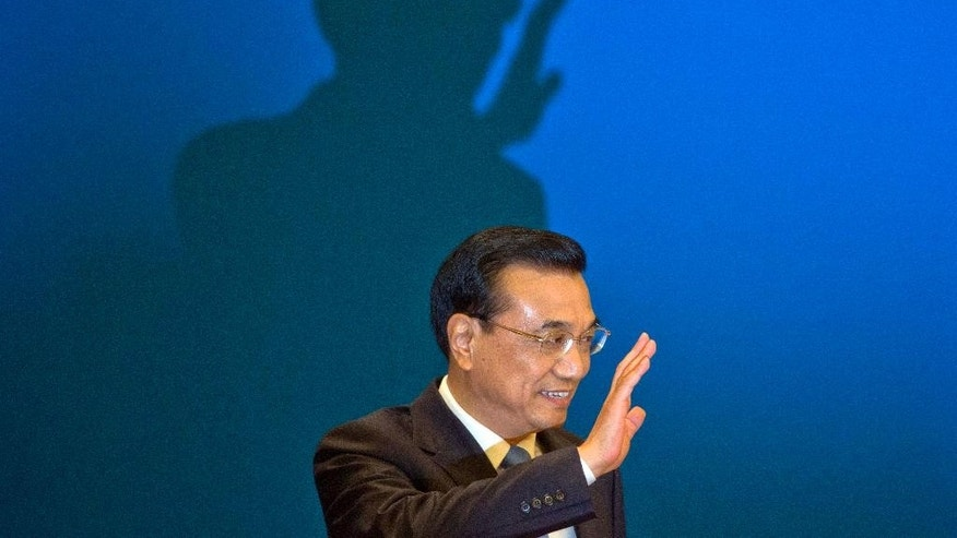 FILE - In this March 15, 2015, file photlo, Chinese Premier Li Keqiang waves as he arrives for a press conference at the end of the National People's Congress in Beijing's Great Hall of the People. Li Keqiang will accelerate plans for an ambitious railway linking Brazil's Atlantic coast with a Pacific port in Peru, and announce billions in other investments and trade deals, when he visits Brasilia on Tuesday, May 19, 2015, kicking off a four-nation South American tour that includes Chile, Peru and Colombia. (AP Photo/Ng Han Guan, File)