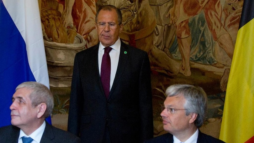 Russian Foreign Minister Sergey Lavrov, center, looks on as Belgian Foreign Minister Didier Reynders, right, and Russia's Vice-Minister of Finance Sergei Shatalov prepare to sign a taxation agreement on the sidelines of the Council of Europe at the Egmont Palace in Brussels on Tuesday, May 19, 2015. The Council of Europe meets Tuesday with ministers of state to discuss terrorism. (AP Photo/Virginia Mayo)