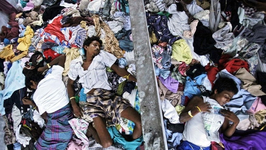 Ethnic Rohingya men take a nap on a pile of clothes donated by local residents at a temporary shelter in Langsa, Aceh province, Indonesia, Sunday, May 17, 2015. Boatloads of more than 2,000 migrants — ethnic Rohingya Muslims fleeing persecution in Myanmar and Bangladeshis trying to escape poverty — have landed in Indonesia, Malaysia and Thailand in recent weeks. Aid groups estimate that thousands more are stranded at sea after a crackdown on human traffickers prompted captains and smugglers to abandon their human cargo. (AP Photo/Binsar Bakkara)