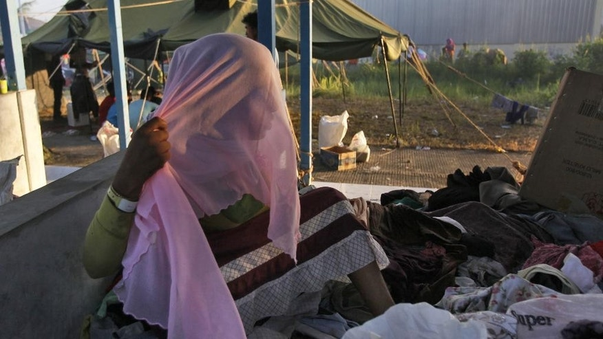 An ethnic Rohingya women tries on a Muslim headscarf she found in a pile of clothes donated by local residents at a temporary shelter in Langsa, Aceh province, Indonesia, Monday, May 18, 2015. More than 2,000 migrants, ethnic Rohingya Muslims fleeing persecution in Myanmar and Bangladeshis trying to escape poverty,  have landed by boat in Indonesia, Malaysia and Thailand in recent weeks, and aid groups estimate that thousands more are stranded at sea after a crackdown on human traffickers prompted captains and smugglers to abandon their human cargo. (AP Photo/Binsar Bakkara)