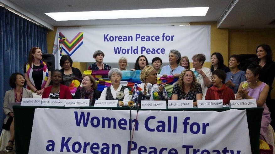 Members of the Women Cross DMZ group sing a song during a press conference before they leave for Pyongyang, at a hotel in Beijing, China, Tuesday, May 19, 2015. A group of 30 women from around the world, headed by U.S. activist Gloria Steinem, are planning to walk across the 2-mile (3.2 kilometer) wide Korean Peninsula's heavily-mined DMZ from north to south on May 24 in a symbolic act of peace. (AP Photo/Andy Wong)