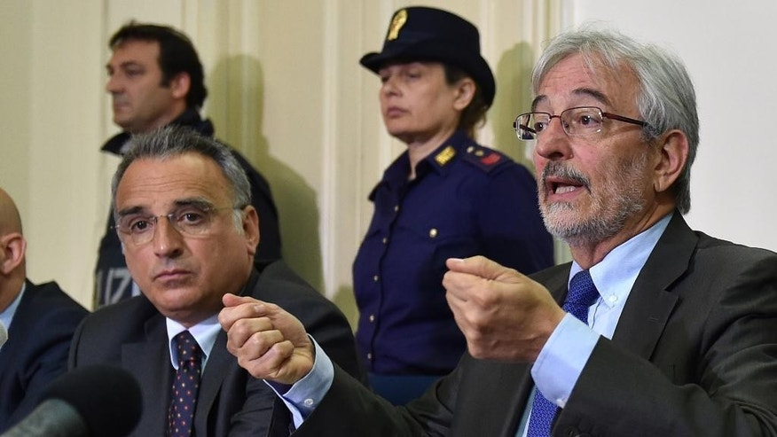 Italian prosecutor Giovanni Salvi, right, is flanked by Catania Police chief Marcello Cardona as he speaks during a press conference in Catania, Sicily, Southern Italy, Tuesday, May 19, 2015. Giovanni Salvi says authorities have dropped a possible charge of illegal detention against two alleged smugglers being held in connection with a shipwreck believed to have killed more than 800 migrants. Prosecutor Giovanni Salvi told reporters Tuesday that investigators now believe that the doors were closed to secure the boat and not to detain hundreds of migrants on two lower decks as prisoners. Many of the victims were believed to have perished closed inside the overcrowded fishermen's boat when it sank near the Libyan coast on April 18. (AP Photo/Carmelo Imbesi)