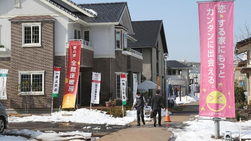 In this Feb. 17, 2014 file photo, people walk by model houses in Yokohama near Tokyo. Japan said its economy expanded at a faster-than-expected 2.4 percent annual rate in January-March, thanks largely to a rebound in housing construction.  The government reported Wednesday, May 20, 2015,  that preliminary estimates show the world's third-biggest economy expanded 0.6 percent from the previous quarter. It was the second straight quarter of growth following a recession in mid-2014 brought on by a sales tax hike that crippled private demand.(AP Photo/Koji Sasahara, File)
