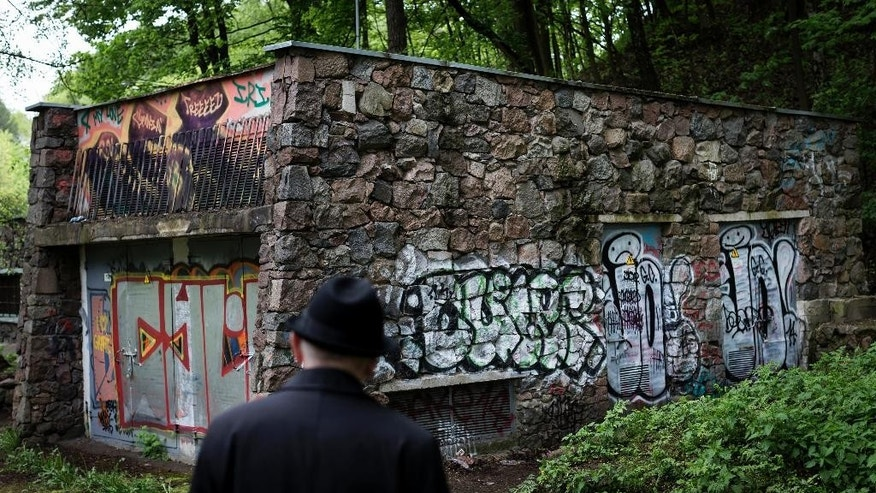 In this photo taken on Wednesday, May  13, 2015, Shmuel Levin, the Chairperson of the Jewish religious Community of Vilnius and Lithuania, looks at the power substation built of tombstones from a Jewish cemetery in Vilnius, Lithuania. Tombstones from a Jewish cemetery were used to build a power substation in the 1960s.  City officials now want to tear it down and return the tombstones to Lithuania's tiny Jewish community, which was nearly wiped out during the Holocaust. They're also investigating whether there are other examples of Jewish tombstones being used as building material during the Soviet occupation, when the communist authorities paid little attention to religious symbols. (AP Photo/Mindaugas Kulbis)