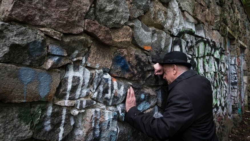 In this photo taken on Wednesday, May  13, 2015, Shmuel Levin, the Chairperson of the Jewish religious Community of Vilnius and Lithuania, leans against a wall of the power substation built of tombstones from a Jewish cemetery in Vilnius, Lithuania. Tombstones from a Jewish cemetery were used to build a power substation in the 1960s.  City officials now want to tear it down and return the tombstones to Lithuania's tiny Jewish community, which was nearly wiped out during the Holocaust. They're also investigating whether there are other examples of Jewish tombstones being used as building material during the Soviet occupation, when the communist authorities paid little attention to religious symbols. (AP Photo/Mindaugas Kulbis)