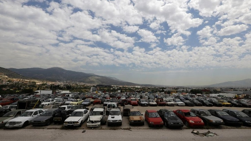 Hundreds of cars are parked at the Public Property Management Organization (ODDY) during an auction in northwestern Athens on Tuesday, May 19, 2015. The ODDY frequently auctions state and confiscated vehicles with hundreds of people trying to buy them at low prices. Greek Finance Minister Yanis Varoufakis said Monday that he expects an agreement with bailout creditors within the next week, which would save the cash-strapped country from fast-approaching bankruptcy. (AP Photo/Thanassis Stavrakis)