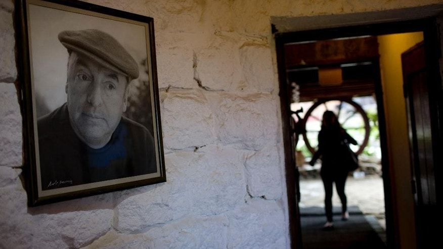 In this April 26, 2015 photo, a framed photo of Nobel Prize-winning poet Pablo Neruda hangs on a wall, as a tourist enters his favorite home in Isla Negra, Chile. In a statement released to The Associated Press Tuesday, May 19, 2015, Chile's Neruda Foundation said that more than two years after Neruda was exhumed to determine the cause of his death, it's time for the poet to rest in peace in his home in the coastal town of Isla Negra. The foundation is demanding that the remains of Neruda be reburied immediately.(AP Photo/Natacha Pisarenko)