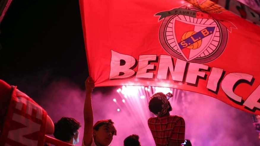 A young Benfica supporter waves his team flag as he celebrates with others after Benfica won the Portuguese league championship at the Marques Pombal square, in Lisbon, Sunday, May 17, 2015. Benfica clinched its 34th league title after a 0-0 draw against Vitoria Guimaraes with one round left to play. (AP Photo/Francisco Seco)