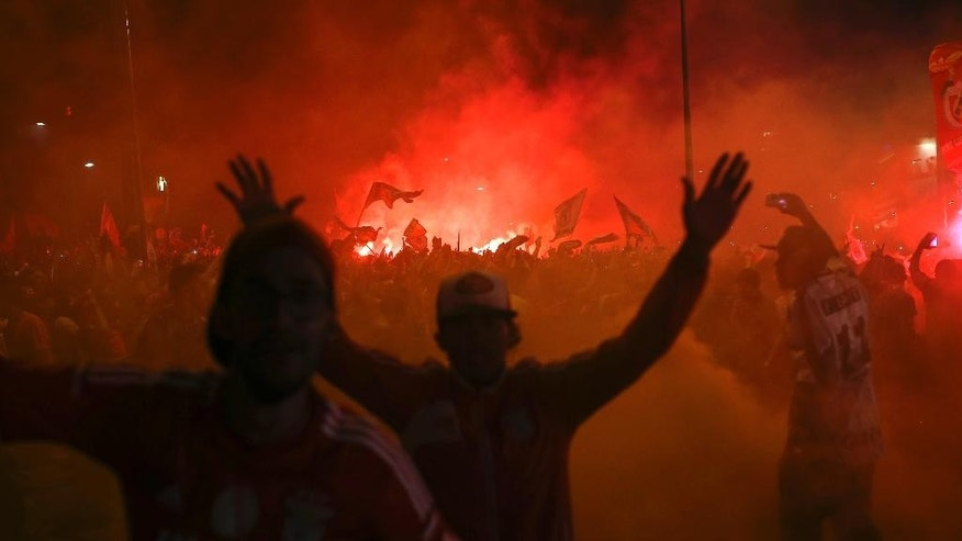 Benfica supporters light flares as they celebrate after Benfica won the Portuguese league championship at the Marques Pombal square, in Lisbon, Sunday, May 17, 2015. Benfica clinched its 34th league title after a 0-0 draw against Vitoria Guimaraes with one round left to play. (AP Photo/Francisco Seco)