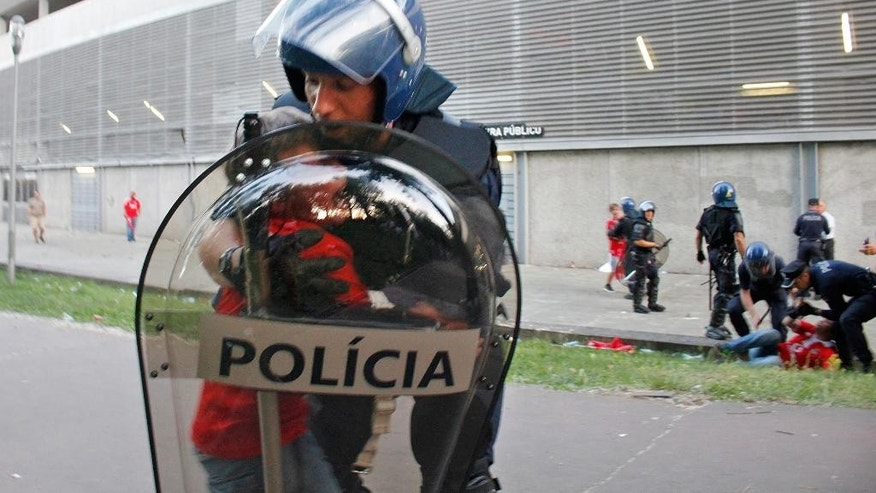 In this May 17 2015 photo, a riot policeman holds a crying boy as his father is attacked by other policemen with batons, right, outside of a stadium, in Guimaraes, Portugal. Portuguese prosecutors are investigating a policeman who beat a man in front of his young children and punched their grandfather outside a soccer stadium, sparking a national scandal. Police approached Jose Magalhaes, his two sons and his father Sunday outside Guimaraes stadium, where Benfica had just won the Portuguese league title, according to film footage and witness reports. (AP Photo/Delfim Machado)