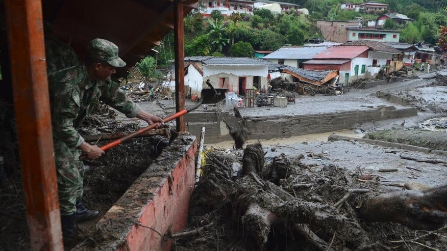 A soldier shovels mud from a house damaged by a mudslide in Salgar, in Colombia's northwestern state of Antioquia, Tuesday, May 19, 2015.  The avalanche of mud and debris roared through the mountain town before dawn Monday, taking away homes and bridges. Authorities said the death toll, which had risen to 62, was likely to grow throughout the day as an undetermined number of people remain missing. (AP Photo/Luis Benavides)
