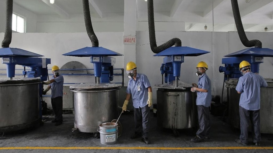 In this Wednesday, May 6, 2015 photo, workers in masks and safety helmets inspect mixing machines at GMM non-stick coatings factory in Zhuhai, Guangdong province, China. In China, where the yuan has risen in tandem with the dollar because of Beijing's tight control, manufacturers like GMM, which has a factory in Zhuhai and another in India, are losing some overseas sales. (AP Photo/Vincent Yu)
