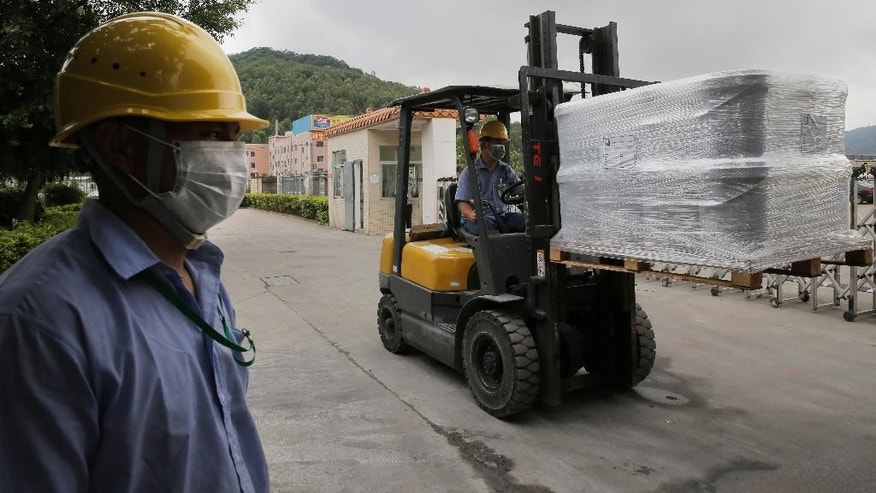 In this photo taken Wednesday, May 6, 2015, workers load a truck with pallets of product at GMM non-stick coatings factory in Zhuhai, Guangdong province, China. In China, where the yuan has risen in tandem with the dollar because of Beijing's tight control, manufacturers like GMM, which has a factory in Zhuhai and another in India, are losing some overseas sales. (AP Photo/Vincent Yu)