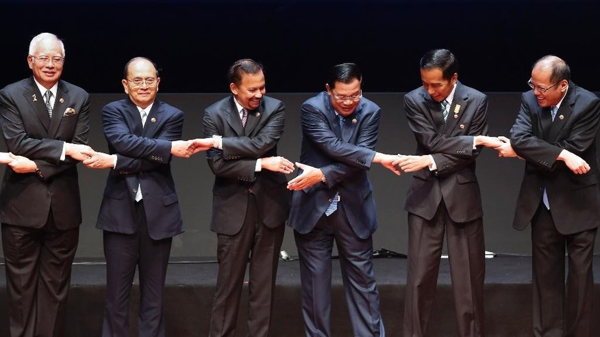 In this April 27, 2015, file photo, from left to right, Malaysia's Prime Minister Najib Razak, Myanmar's President Thein Sein, Brunei's Sultan Hassanal Bolkiah, Cambodia's Prime Minister Hun Sen, Indonesia's President Joko Widodo and Philippine's President Benigno Aquino III join their hands during the opening ceremony for the 26th ASEAN Summit in Kuala Lumpur, Malaysia. For years, the Southeast Asian grouping known as ASEAN has come under fire for being a toothless organization for its bedrock policy of staying out of each other's internal affairs, and for ignoring the plight of Myanmar's persecuted Rohingya minority. Now, a spiraling humanitarian crisis involving thousands of Rohingya and Bangladeshis stranded at sea, one of the region's most serious problems since the Vietnam War, has brought those two realities into sharp focus under the uncomfortable glare of the international spotlight. (AP Photo/Vincent Thian, File)