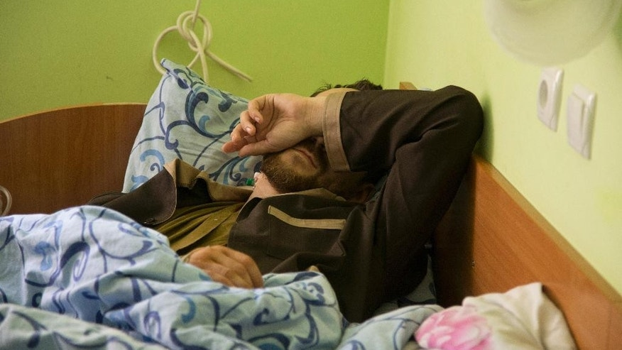 Captain Yevgeny Yerofeyev of the Russian special forces covers his face by his hand as he lies in a military hospital bed, in Kiev, Ukraine, Tuesday, May, 19, 2015. Two wounded Russian soldiers captured while fighting in war-torn eastern Ukraine have been transferred to a hospital in Kiev, Ukrainian officials said Monday as Moscow once again firmly denied any involvement in the fighting. (AP Photo/Efrem Lukatsky)