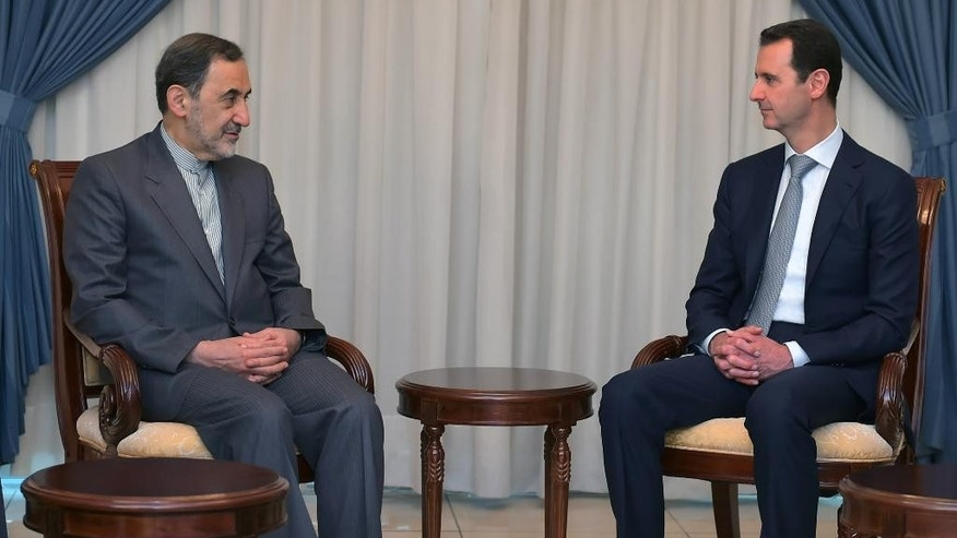 In this photo released by the Syrian official news agency SANA, Syrian President Bashar Assad, right, meets with Ali Akbar Velayati, an adviser to Iran's Supreme Leader Ayatollah Ali Khamenei, in Damascus, Syria, Tuesday, May 19, 2015. (SANA via AP)
