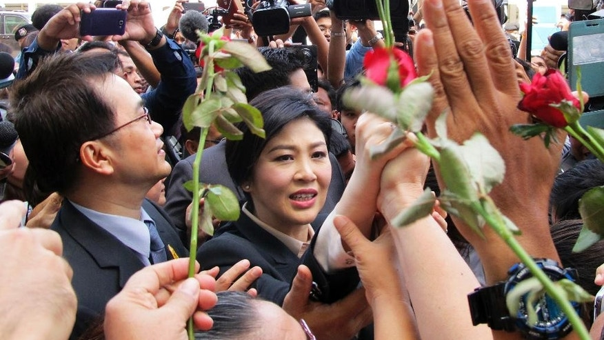 Thailand's former Prime Minister Yingluck Shinawatra, center, walks through supporters as she leaves the Supreme Court in Bangkok, Thailand, Tuesday, May 19, 2015. Yingluck entered a plea of not guilty Tuesday after she was charged with dereliction in overseeing a controversial rice subsidy program that lost billions of dollars. If found guilty she could be jailed for a decade, which critics say is part of a politically motivated campaign against her family. (AP Photo/Thanyarat Doksone)