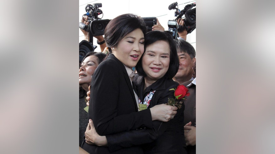 Thailand's former Prime Minister Yingluck Shinawatra, left, is embraced by a supporter as she arrives at the Supreme Court in Bangkok, Thailand, Tuesday, May 19, 2015. Yingluck entered a plea of not guilty Tuesday after she was charged with dereliction in overseeing a controversial rice subsidy program that lost billions of dollars. If found guilty she could be jailed for a decade, which critics say is part of a politically motivated campaign against her family.  (AP Photo/Thanyarat Doksone)