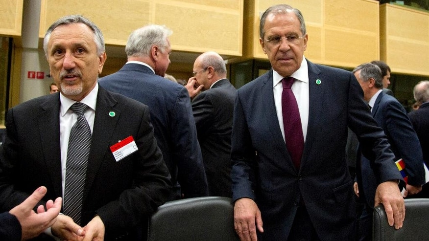 Foreign Minister Pasquale Valentini, of San Marino, left, and Russian Foreign Minister Sergey Lavrov, right, wait for the start of a formal session of the Council of Europe at the Egmont Palace in Brussels on Tuesday, May 19, 2015. The Council of Europe meets Tuesday with ministers of state to discuss terrorism. (AP Photo/Virginia Mayo)