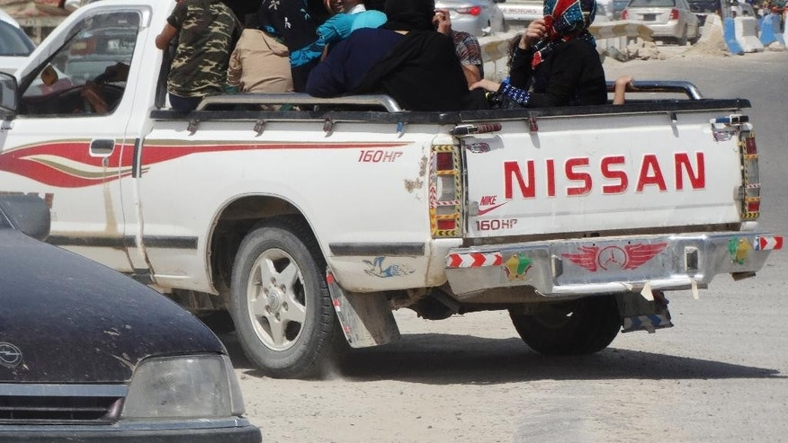 In this Monday, May 18, 2015 photo, civilians fleeing their hometown of Ramadi, Iraq, drive away a police checkpoint as they drive through Habaniyah town, 80 kilometers (50 miles) west of Baghdad. Iraqi forces and allied Sunni tribesmen repelled an Islamic State attack overnight on a town west of Baghdad, a tribal leader said Tuesday, as the government renewed its commitment to arm anti-militant Sunni tribes following the loss of the key city of Ramadi. (AP Photo)