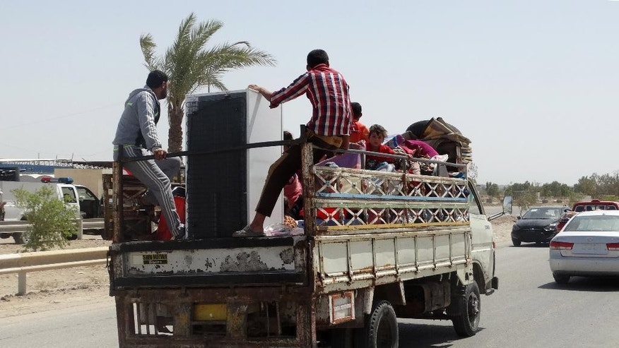In this Monday, May 18, 2015 photo, civilians fleeing their hometown of Ramadi, Iraq, rides on a truck in Habaniyah town, 80 kilometers (50 miles) west of Baghdad. Iraqi forces and allied Sunni tribesmen repelled an Islamic State attack overnight on a town west of Baghdad, a tribal leader said Tuesday, as the government renewed its commitment to arm anti-militant Sunni tribes following the loss of the key city of Ramadi. (AP Photo)
