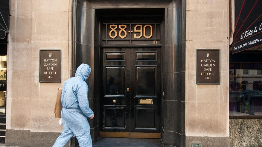 FILE - In this Tuesday, April 7, 2015 file photo, Police forensics officer enter the Hatton Garden Safe Deposit company in London. More than 200 British police swooped down on suspected jewel thieves Tuesday, May 19, 2015, making arrests in the notorious Hatton Garden heist that took place in London over the Easter weekend. Scotland Yard said seven British men, ranging in age from 48 to 76, are being questioned in a London police station after the morning raids. The men were arrested in north London and in Kent, southeast of the city. (Dominic Lipinski/PA via AP, file)      UNITED KINGDOM OUT      -    NO SALES      -     NO ARCHIVES