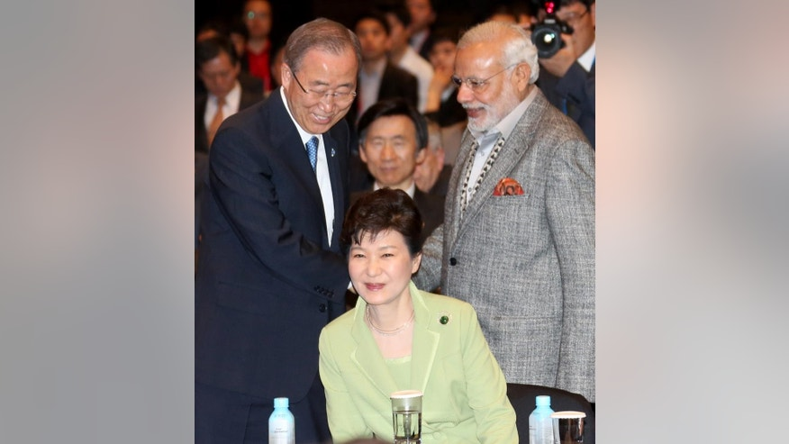 South Korean President Park Geun-hye, bottom, sits as U.N. Secretary General Ban Ki-moon, left, greets Indian Prime Minister Narendra Modi, right, upon their arrival for the Asian Leadership Conference in Seoul, South Korea, Tuesday, May 19, 2015. (Baek Seung-yul/Yonhap via AP) KOREA OUT