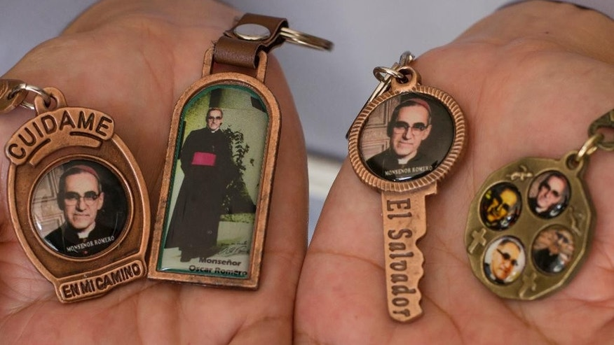 FILE - In this March 11, 2015 file photo a nun holds keychains with images of Archbishop Oscar Arnulfo Romero. The upcoming beatification of El Salvador Archbishop Oscar Romero is doing more than just giving Latin America its long-awaited saint-in-waiting. It has helped redefine the Catholic Church's concept of martyrdom and paved the way for others killed for doing God's work to follow in Romero's saint-making footsteps. (AP Photo/Salvador Melendez, File)