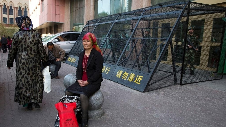 FILE - In this May 1, 2014 file photo, a Uighur woman rests near a cage protecting heavily armed Chinese paramilitary policemen on duty in Urumqi in China's northwestern region of Xinjiang. While most Chinese can easily obtain passports, eroding barriers to travel have thrown into relief a new pattern showing that entire ethnic groups deemed potentially risky to the leadership - such as Muslim Uighurs and Buddhist Tibetans - are largely being barred. By denying them opportunities for jobs, education and overseas connections, the withholding of passports has become one of the party's most potent weapons against dissent, both real and imagined. (AP Photo/Ng Han Guan, File)