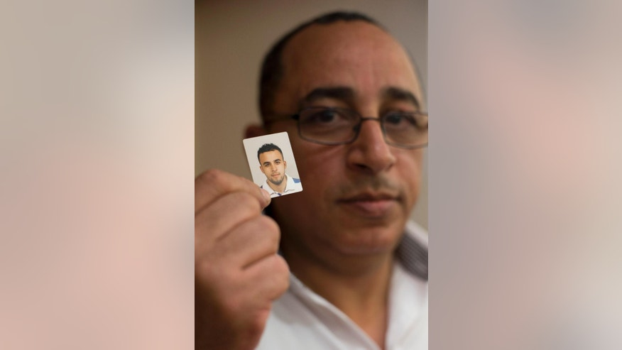 Mohamed Nidalha poses with a passport photo of his son Reda during an interview on Friday, May 15, 2015, in Leiden, Netherlands. Nidalha's 20-year-old son Reda, who grew up liking girls and going to discos, suddenly changed thanks to a toxic cocktail of online propaganda and covert contact with extremists in Belgium, one of Europe's hotspots for Islamic radicals, and eventually traveled to Syria. Reda is emblematic for hundreds of disaffected Muslim youngsters from the largely secular countries of Belgium and the Netherlands who have turned their backs on their liberal Western societies and been sucked into the sectarian maelstrom of Syria's brutal civil war. (AP Photo/Peter Dejong)