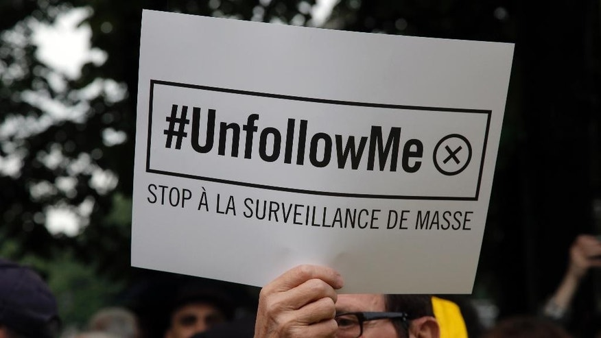 "FILE - In this May 4, 2015 file photo, a demonstrator holds a placard that reads: ""Stop to Mass Surveillance"", during a gathering at Invalides, Paris, to protest against the emergency government surveillance law. Fearful of an expanding extremist threat, countries that for years have relied heavily on U.S. intelligence are quickly building up their own capabilities with new technology, new laws and _ in at least one case _ a searing debate on how much the American government should be allowed to spy on their own citizens. (AP Photo/Francois Mori, File)"
