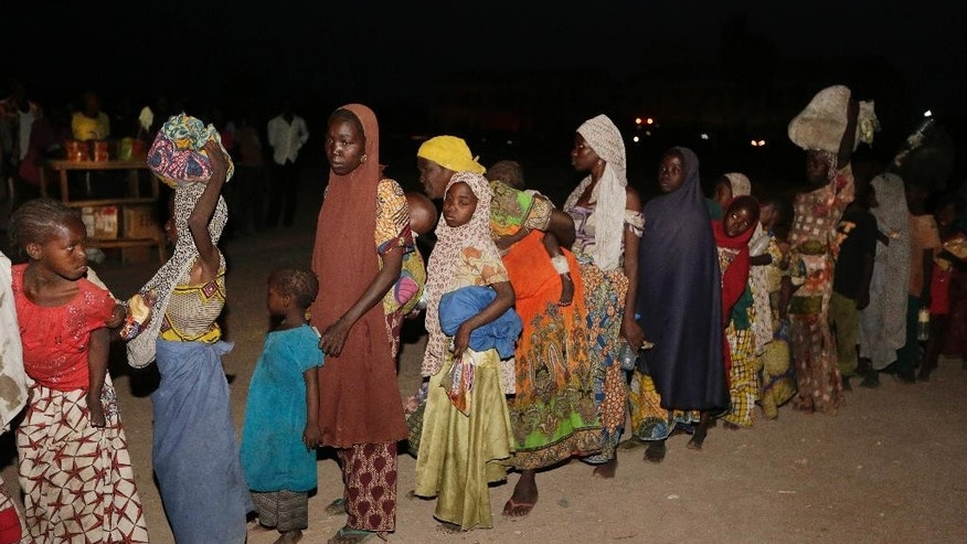 FILE - In this Saturday May 2, 2015 file photo, women and children rescued by Nigeria soldiers from Islamist extremists at Sambisa forest arrive at a camp for the displaced people in Yola, Nigeria. All 275 women, girls and children rescued from Boko Haram and taken to the safety of a northeast Nigerian refugee camp have been taken into military custody amid suspicions that some are aiding the Islamic extremists, a camp official and a Nigerian military intelligence officer said Wednesday May 20, 2015. (AP Photo/Sunday Alamba, File)