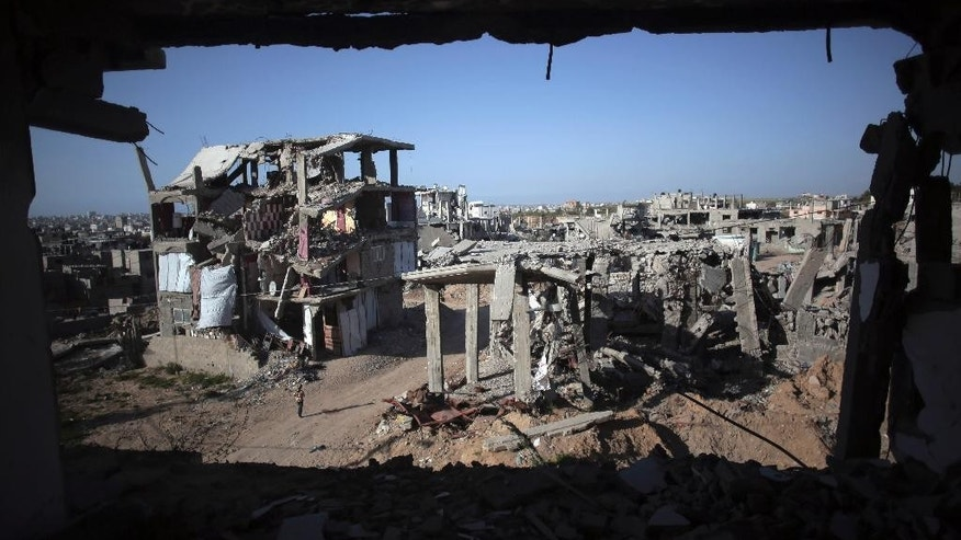 """File - In this March 30, 2015 file photo, a Palestinian girl walks next to destroyed houses, in the Shijaiyah neighborhood of Gaza City. The International Monetary Fund said in a Tuesday, May, 19, 2015 report, that reconstruction of the Gaza Strip is going """"far more slowly than expected"""" after a devastating war between Israel and the Hamas militant group last year. The IMF said that just over a quarter of $3.5 billion pledged for reconstruction has been disbursed and urged donors to fulfill their pledges.  (AP Photo/Khalil Hamra, File)"""