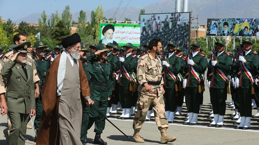 In this picture released by an official website of the office of the Iranian supreme leader on Wednesday, May 20, 2015, Supreme Leader Ayatollah Ali Khamenei, second left, reviews Revolutionary Guard cadets in a graduation ceremony in Tehran, Iran, as he is accompanied by army commander Ataollah Salehi, left. Iran's supreme leader vowed Wednesday he will not allow international inspection of Iran's military sites or access to Iranian scientists under any nuclear agreement with world powers. (Office of the Iranian Supreme Leader via AP)