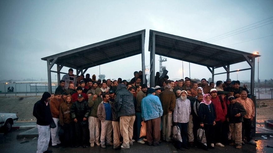 File - In this Nov. 3, 2009 file photo, Palestinian workers stand under a shelter to keep dry from the rain as they wait for transportation after crossing from the West Bank town of Qalqilya to work in Israel, at the Israeli army's checkpoint near Kibbutz Eyal in central Israel. Israeli Prime Minister Benjamin Netanyahu on Wednesday, May 20, 2015, called off a proposed plan to segregate Palestinians from Israelis on West Bank buses, overruling his defense minister amid a flurry of criticism in an attempt to avert the first crisis of his new government. (AP Photo/Oded Balilty, File)