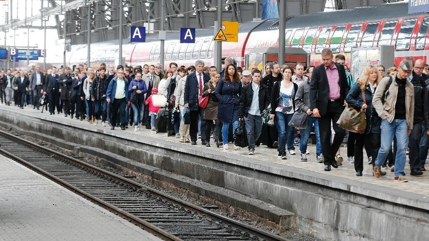 Passengers walk along a platform in the main train station after leaving one of the few running trains as German train drivers went on a strike for an unlimited period in Frankfurt, Germany, Wednesday, May 20, 2015. (AP Photo/Michael Probst)