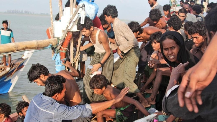 An Acehnese fisherman, lower left, help migrants to transfer to his boat on the sea off East Aceh, Indonesia, Wednesday, May 20, 2015. Hundreds of migrants stranded at sea for months were rescued and taken to Indonesia, officials said Wednesday, the latest in a stream of Rohingya and Bangladeshi migrants to reach shore in a growing crisis confronting Southeast Asia. (AP Photo/S. Yulinnas)