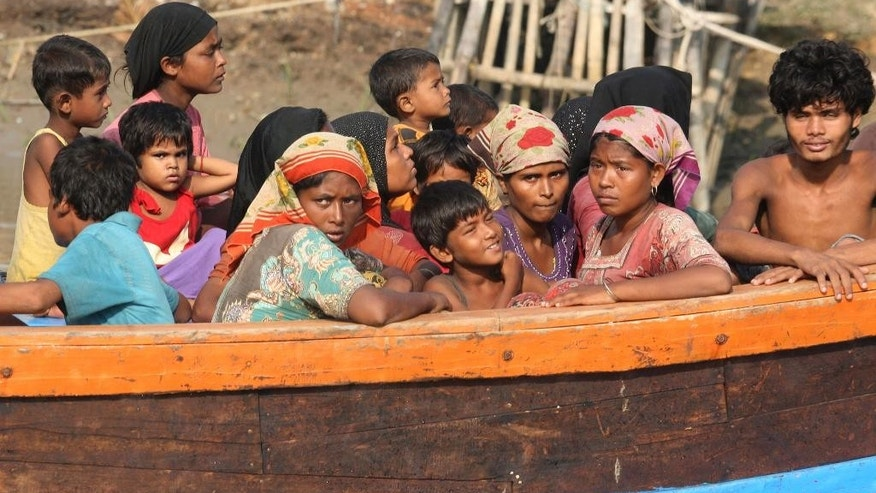 Rescued migrants sit on an Acehnese fishing boat upon arrival in Simpang Tiga, Aceh province, Indonesia, Wednesday, May 20, 2015. Hundreds of migrants stranded at sea for months were rescued and taken to Indonesia, officials said Wednesday, the latest in a stream of Rohingya and Bangladeshi migrants to reach shore in a growing crisis confronting Southeast Asia. (AP Photo/Binsar Bakkara)