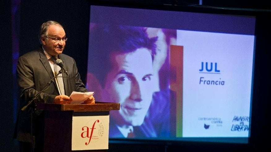 "French ambassador in Nicaragua, Antoine Joly speaks next to a projection with a portrait of French cartoonist Jul during the inauguration ceremony of the  ""Centroamerica Cuenta"" writer's meeting in Managua, Nicaragua, Tuesday, May 19, 2015. Jul was refused entry into Nicaragua by immigration authorities as he arrived to participate in the tribute to Charly Hebdo. (AP Photo/Esteban Felix)"