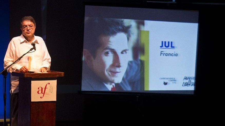 "Nicaraguan writer Sergio Ramirez speaks next to a projection with a portrait of French cartoonist Jul during the inauguration ceremony of the ""Centroamerica Cuenta"" writer's meeting in Managua, Nicaragua, Tuesday, May 19, 2015. Jul was refused entry into Nicaragua by immigration authorities as he arrived to participate in the tribute to Charly Hebdo. (AP Photo/Esteban Felix)"